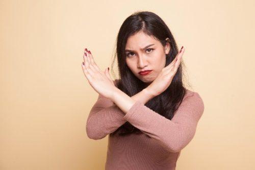 ばつ印を手で作っている女性